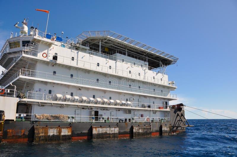 在公海闯入并且用力拖小船,在海湾的油和煤气平台或海,世界能量、近海油和船具建筑 免版税图库摄影