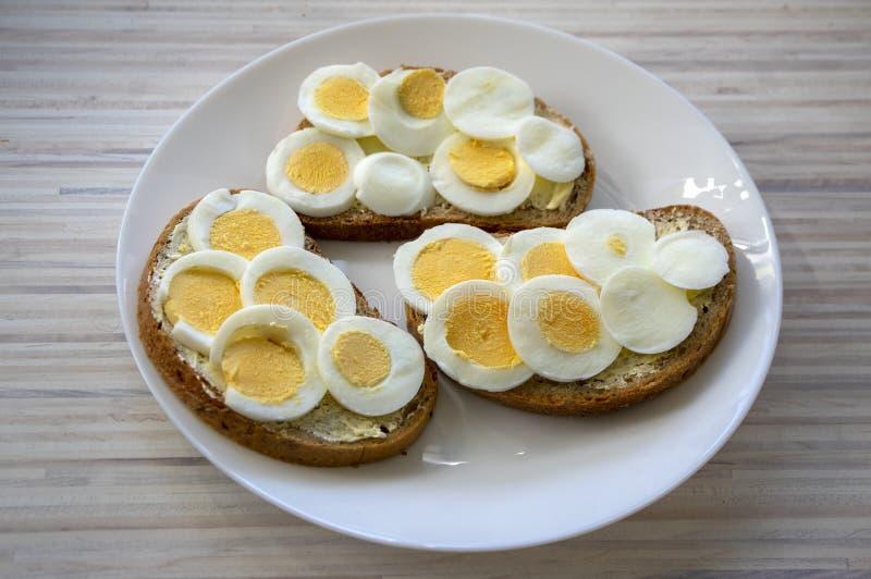 在共同的捷克面包的切的水煮蛋用在白色板材的黄油在轻的木桌上 库存照片