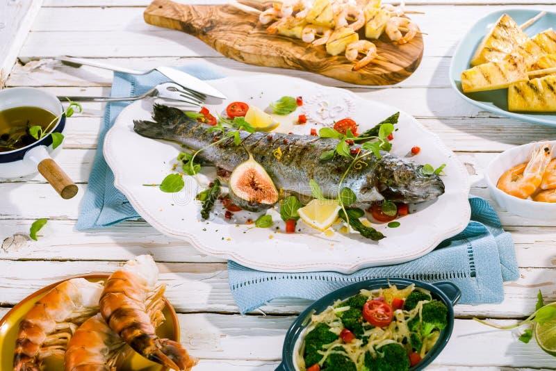 在其他盘中的烤整个鱼在表上 免版税库存图片