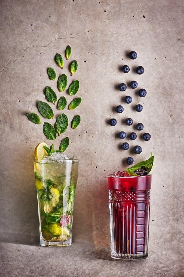 在具体灰色背景的两个夏天鸡尾酒 mojito和蓝莓茶 新冷的饮料概念 r 库存照片