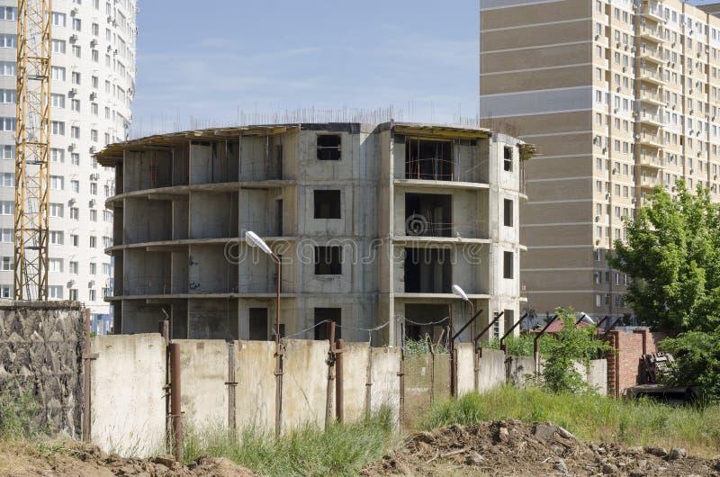 在具体篱芭后建设中的一个圆的大厦位于一个新的大厦的背景 库存图片