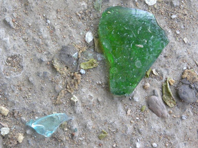 在具体背景的绿色打破的玻璃片断 免版税库存图片