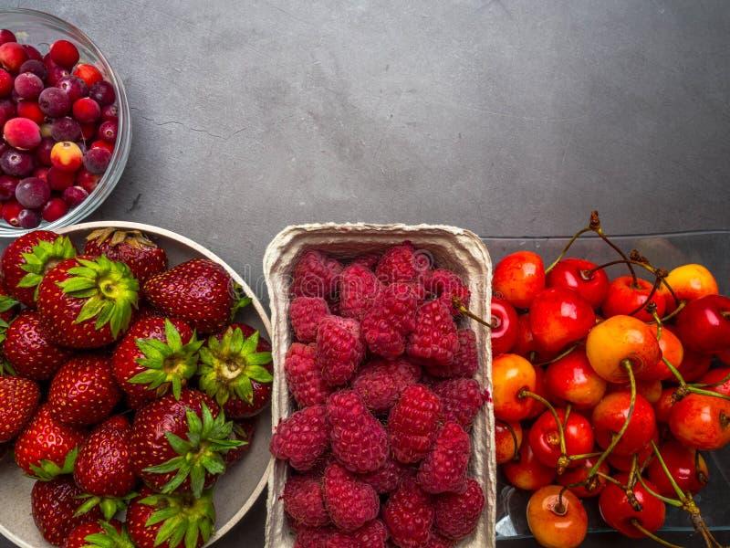 在具体背景的莓果 夏天或春天有机莓果 草莓,莓,樱桃,蔓越桔 r 免版税库存照片
