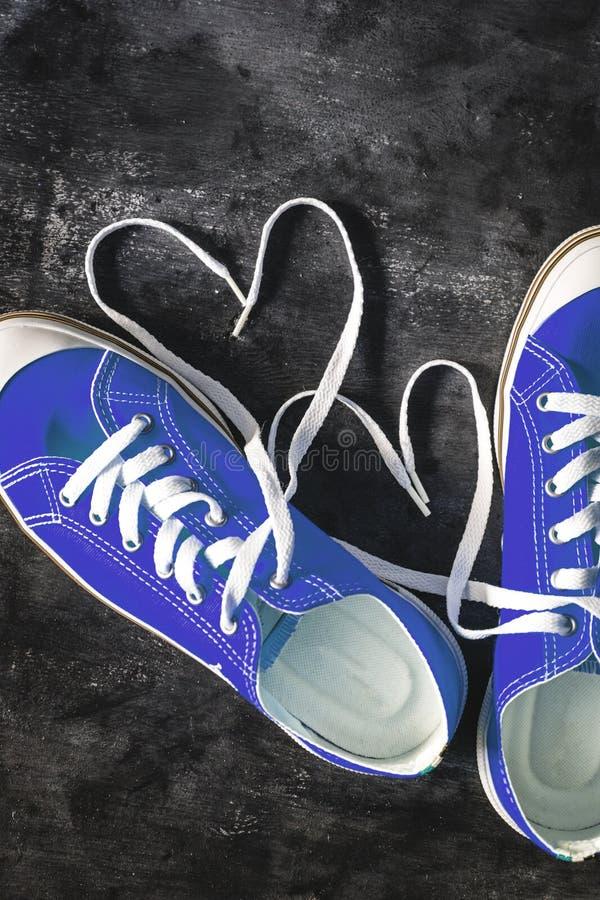 在具体难看的东西黑暗背景和心脏形象的青深蓝运动鞋由鞋带做成 o r ?? 库存照片
