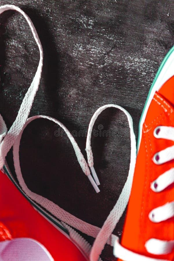 在具体难看的东西黑暗背景和鞋带的心脏的红色运动鞋 o r ?? 图库摄影