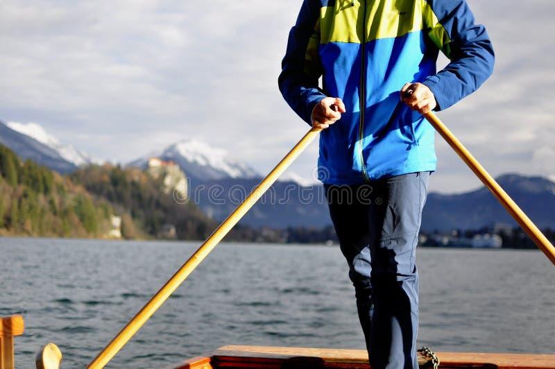 在典型的木小船Pletna的人划船在湖流血,斯洛文尼亚,在日落 旅游业,体育,探索的概念 库存照片