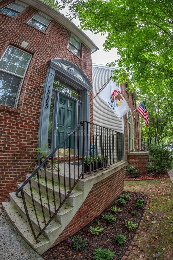 在典型的美国房子前面的美国人和伊利诺伊旗子 免版税库存照片
