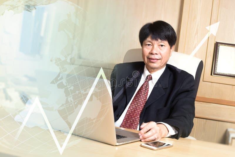 在典雅书桌的看起来的商人亚裔经理资深年龄选址 库存照片