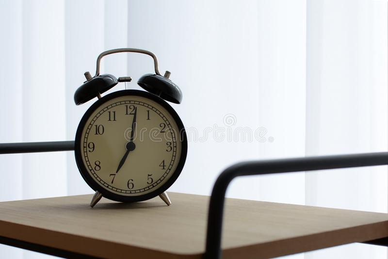 在典雅和现代床头柜上的黑闹钟在与一幅白色帷幕的窗口旁边显示七个小时 免版税库存照片