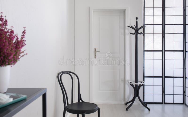 在典雅的公寓,与拷贝空间的真正的照片白色走廊的黑椅子  免版税库存图片