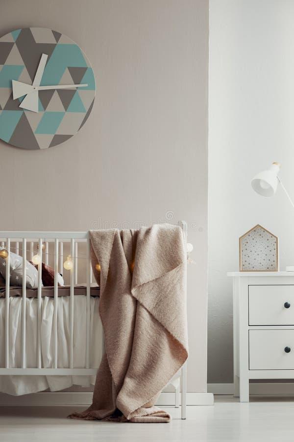 在典雅的婴孩卧室内部墙壁上的花梢噼啪响与白色木小儿床的有粉红彩笔毯子和棉花球光的 免版税库存图片