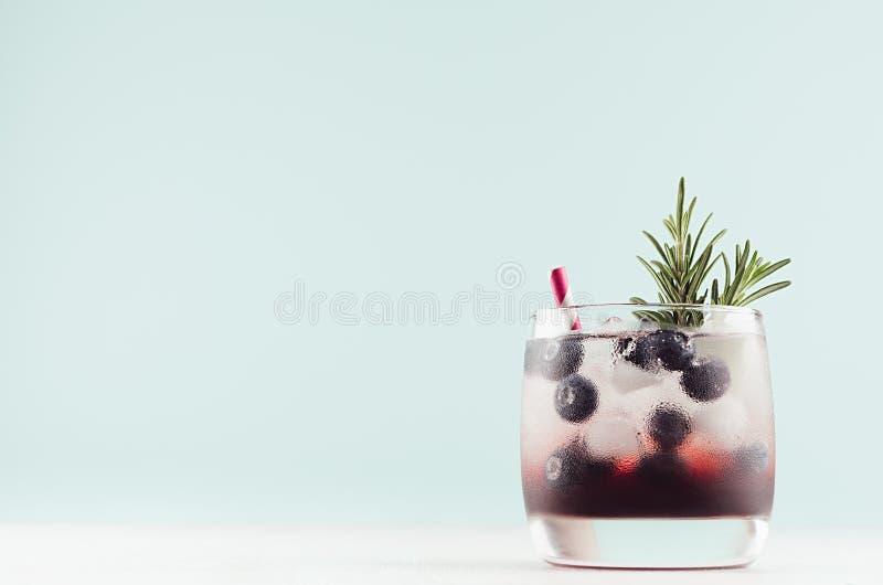 在典雅的玻璃与冰块,蓝莓,在淡色软的绿色背景的迷迭香的甜冷的党饮料 图库摄影