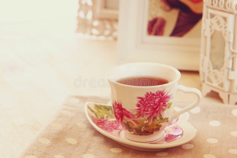 在典雅的葡萄酒瓷杯子的红茶在木桌上 免版税库存图片