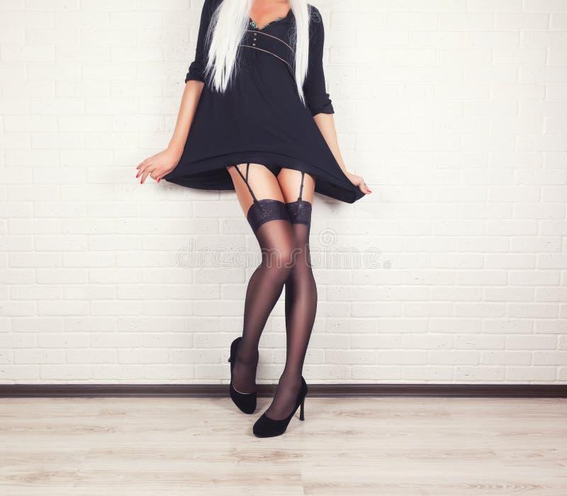 在典雅的黑高跟鞋鞋子的妇女腿 免版税库存照片