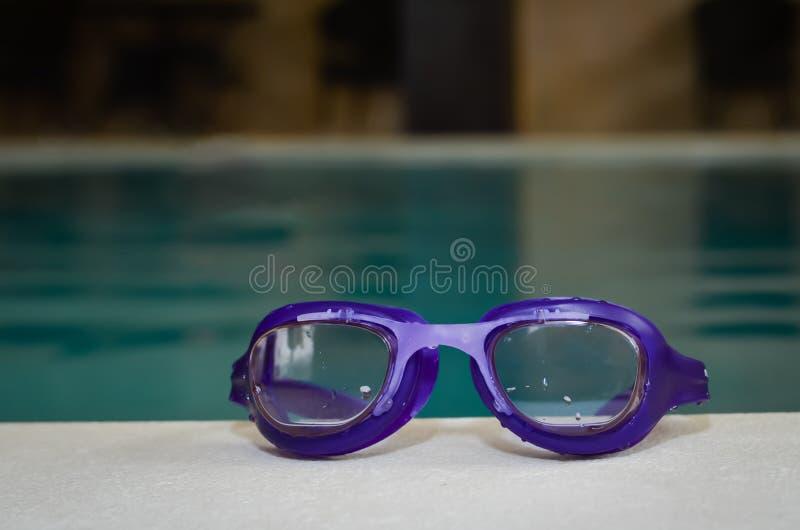 在内部游泳场的边缘的蓝色游泳风镜 免版税库存图片
