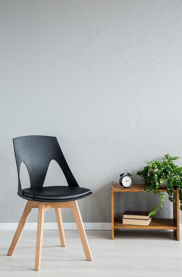 在内阁旁边的典雅的黑木椅子有时钟和花的在现代办公室内部 免版税图库摄影
