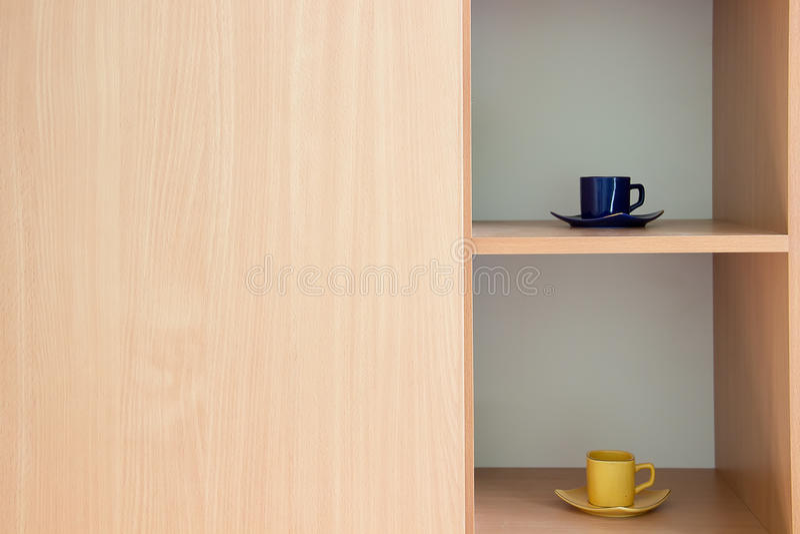 在内阁的两个杯子有轻的木头的 图库摄影