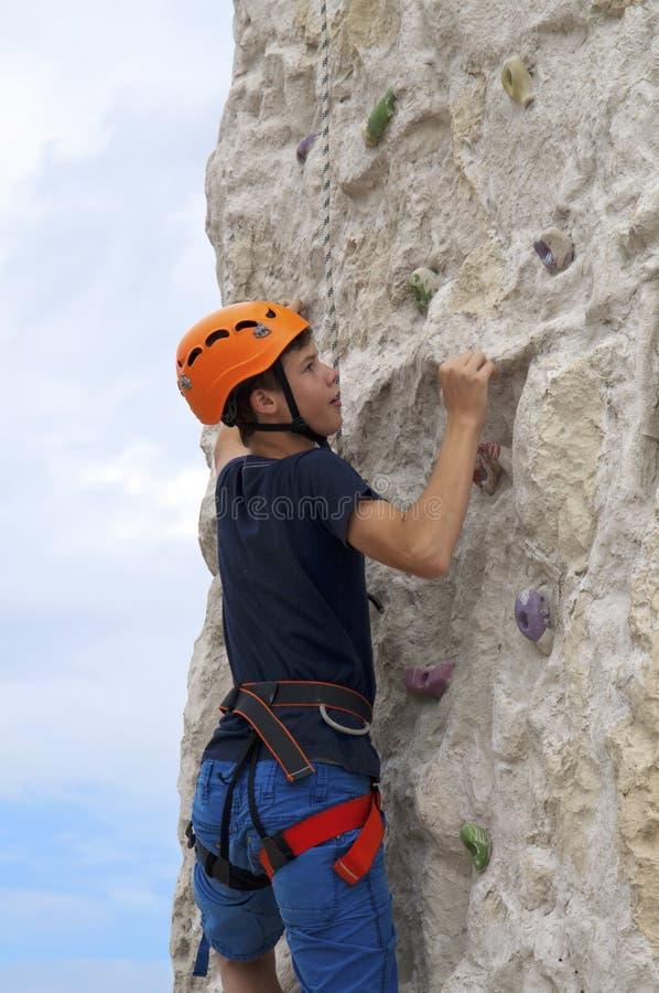 在冒险公园爬上一个年轻的人 免版税库存图片