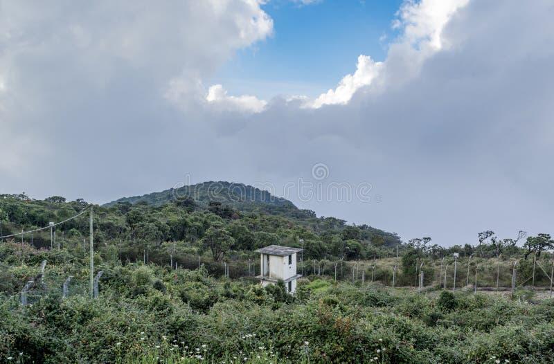 在军事基地的观看的塔与天线位于山 免版税库存照片