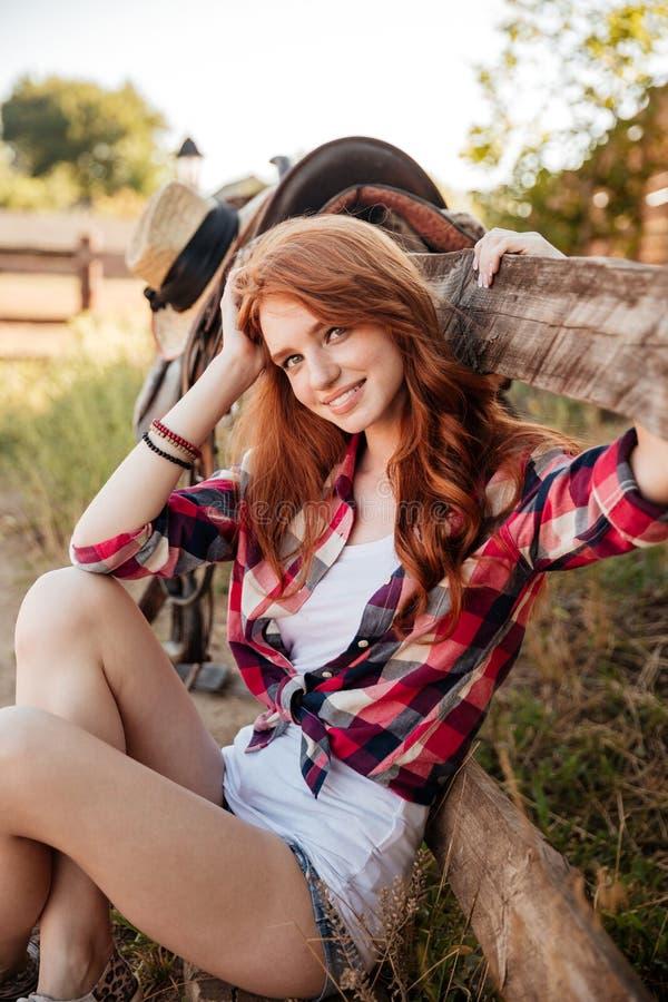 在农场的快乐的逗人喜爱的少妇女牛仔选址 免版税库存照片