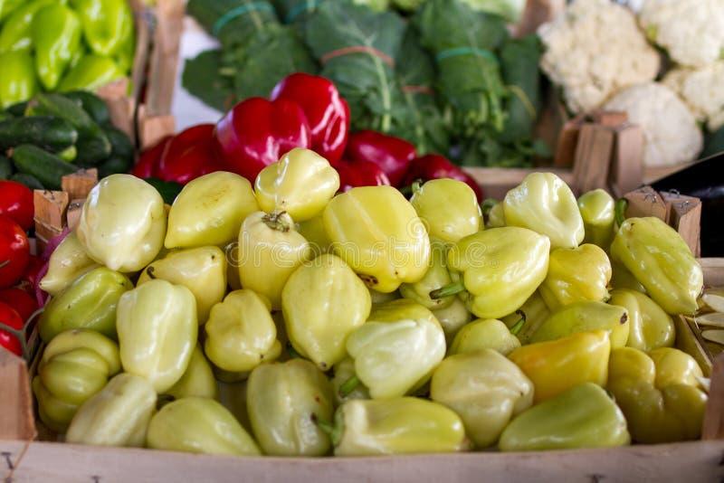 在农夫的市场摊位表立场的黄色和绿色甜椒 免版税库存照片