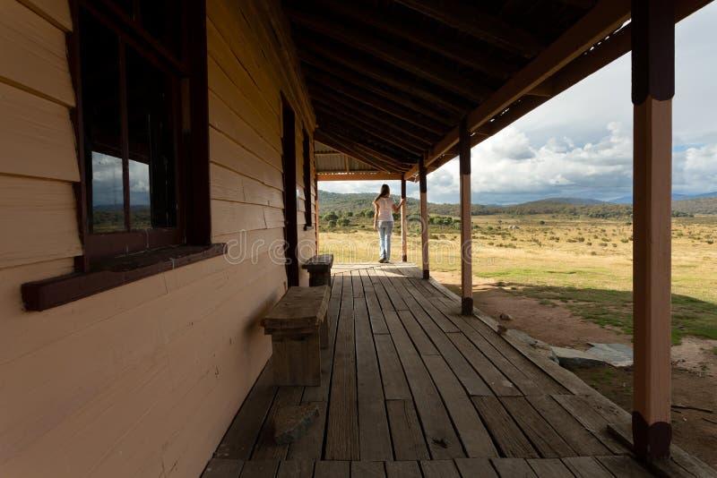 在农村木材宅基游廊的妇女身分在多雪的高平原的 免版税库存图片