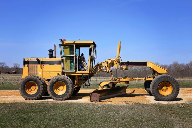 在农村石渣车道的大路平地机建筑卡车工作 图库摄影