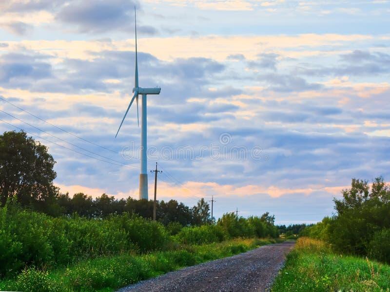 在农村路的风车在日落 可选择能源农厂来源涡轮风 免版税库存照片