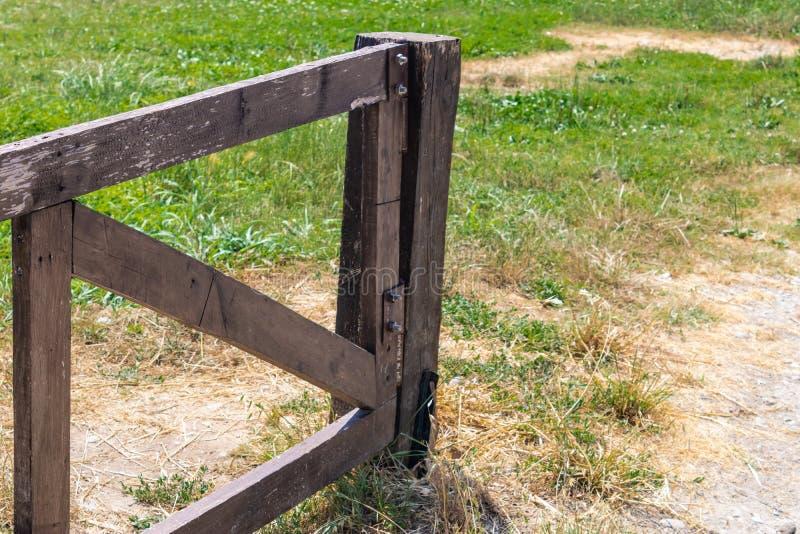 在农田的开放木门有在背景影像的草的 免版税库存图片