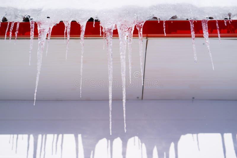 在冬天冰柱在大厦屋顶垂悬