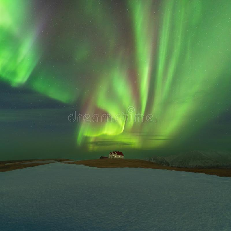 在冬天夜期间,这美丽的北极光或极光borealis在冰岛被采取了在或在凯夫拉维克附近的客舱附近 免版税库存照片