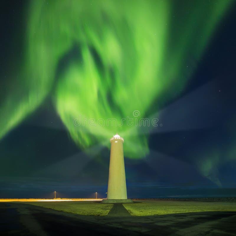 在冬天夜期间,这美丽的北极光或极光borealis在冰岛被采取了在或在凯夫拉维克附近的灯塔附近 免版税库存照片