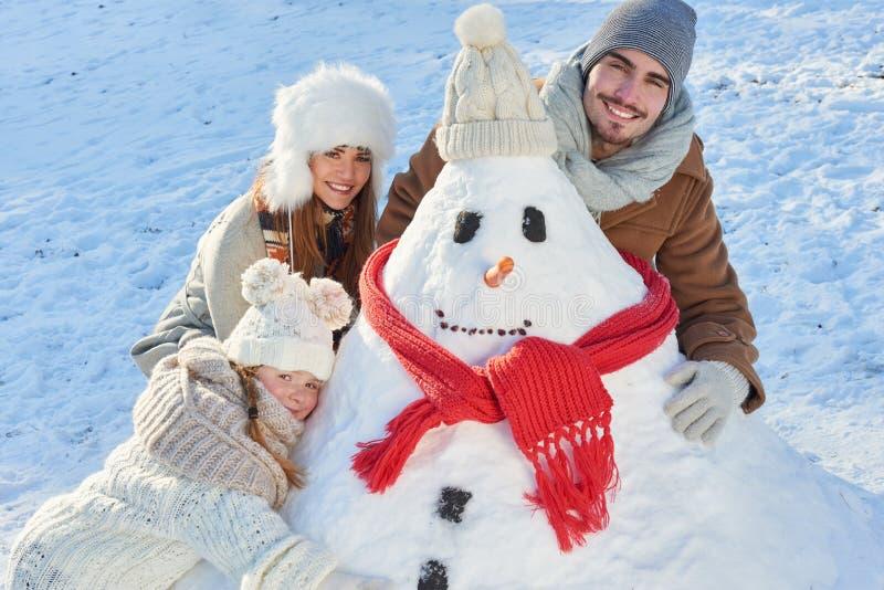 在冬天大厦雪人的愉快的家庭 免版税库存图片