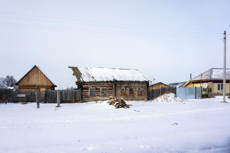 在冬天季节的一个小村庄拉皮条的木 库存照片