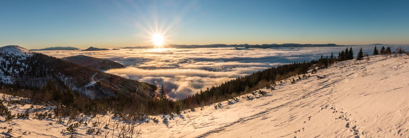 在冬天山土坎的日出在云彩上 免版税库存图片
