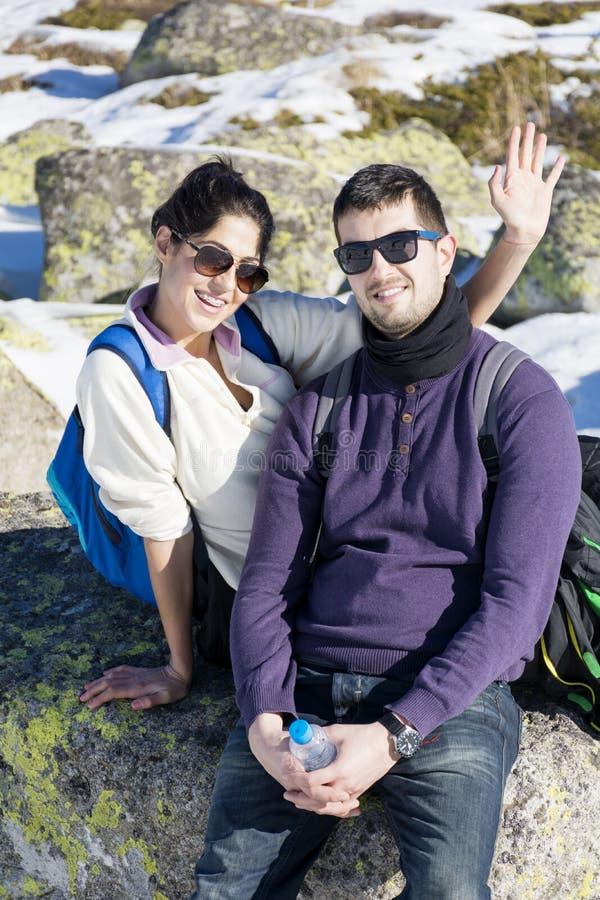 在冬天山的年轻爱夫妇 驱动乐趣爬犁冬天 库存照片