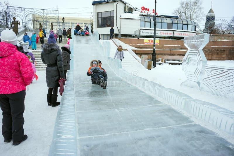 在冬天新年假日期间,有一个孩子的一个爸爸他的胳膊的在克拉斯诺亚尔斯克的中心滚动下来冰冷的小山 库存照片