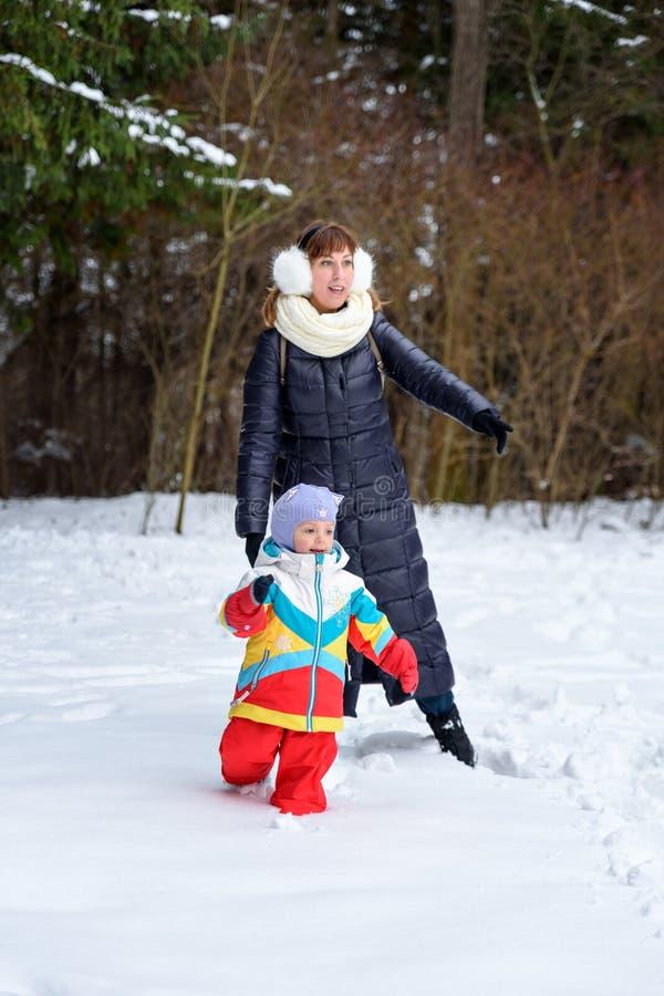 在冬天森林爸爸妈妈和孩子的家庭步行 库存照片