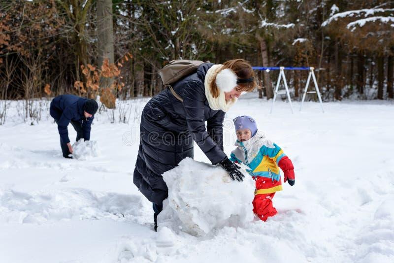 在冬天森林爸爸妈妈和孩子的家庭步行 免版税图库摄影