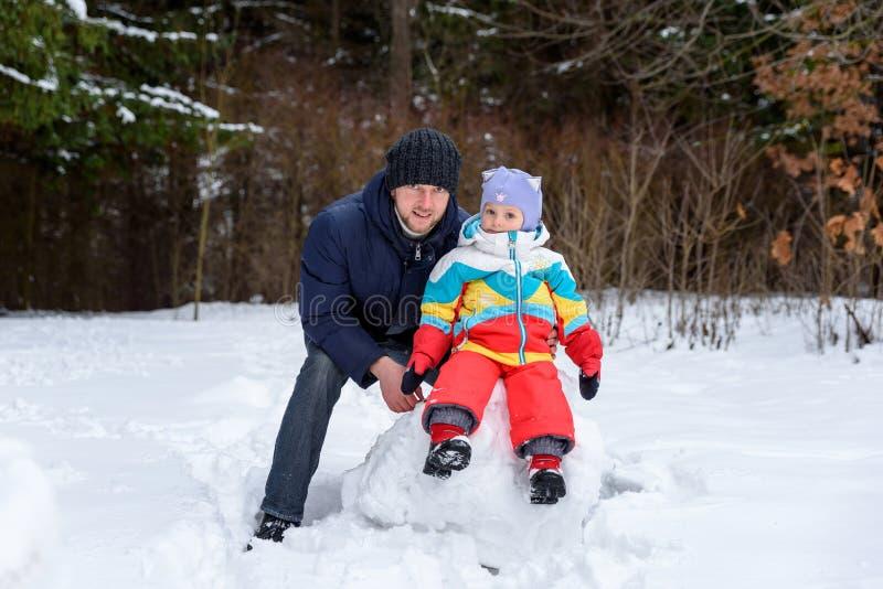 在冬天森林爸爸妈妈和孩子的家庭步行 免版税库存图片