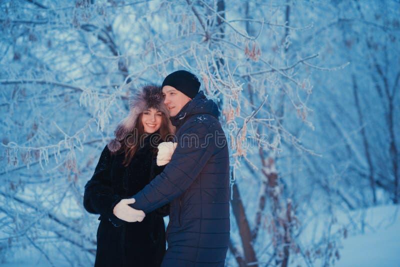 在冬天步行的一对爱恋的夫妇 雪爱情小说,冬天魔术 男人和妇女在冷淡的街道上 人和女孩是休息 免版税库存图片