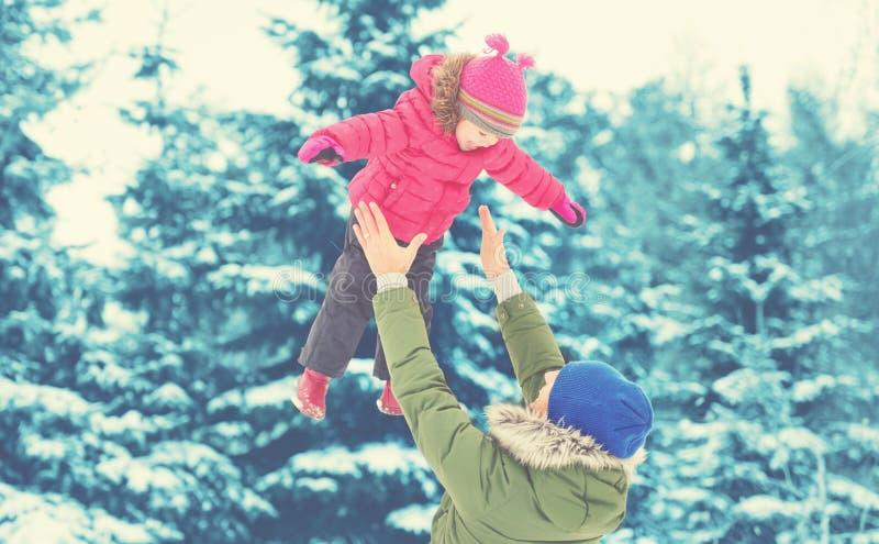 在冬天步行的愉快的家庭 爸爸投掷女婴 免版税库存图片