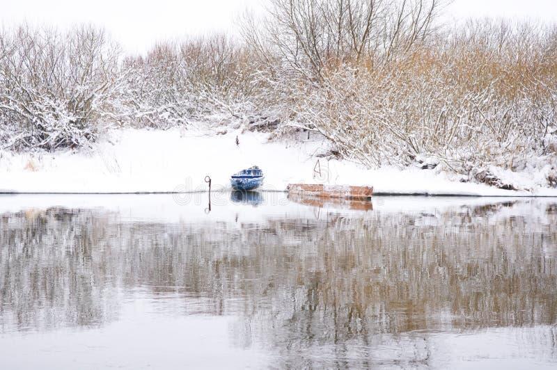 在冬天河岸的小船  免版税库存照片