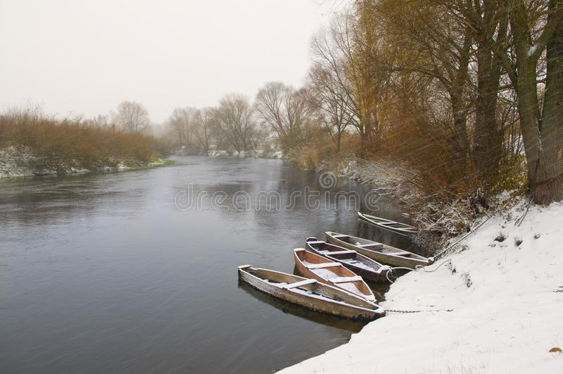 在冬天河的木小船 免版税库存照片