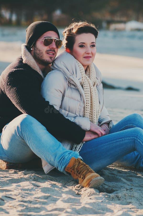 在冬天海滩的可爱的年轻夫妇 库存图片