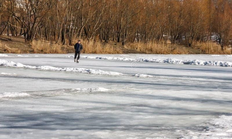 在冬天湖,人们在冰鞋滑冰 横向晴朗的冬天 免版税库存图片