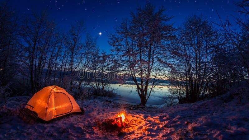 在冬天阵营的有启发性帐篷由湖在晚上 库存照片