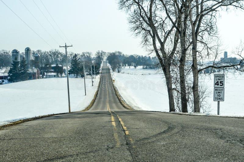 在冬天限速标志的乡下公路 图库摄影