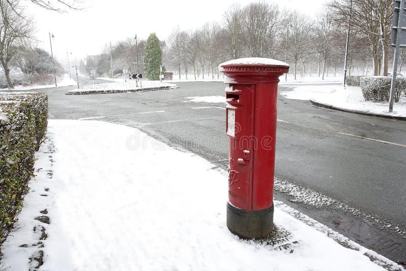 在冬天雪的英国红色过帐配件箱。 免版税库存照片