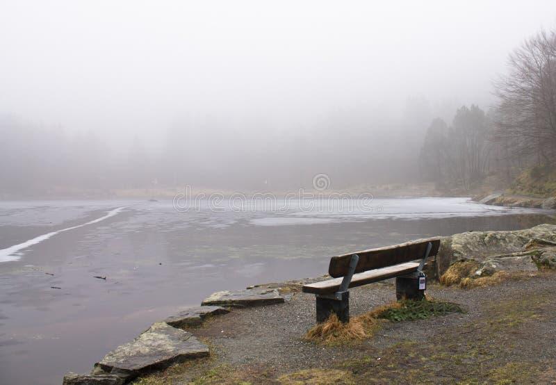 在冬天风景的偏僻的长木凳由有雾的多雨天气的,卑尔根,挪威冻湖 图库摄影